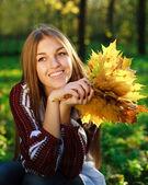 довольно улыбаясь и мечтает девочка держит желтые листья в его руках, в зеленом парке — Стоковое фото