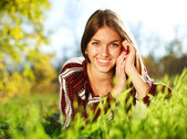Cheerful young girl lying on green grass close up,in summer park. — Stock Photo
