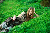 Pretty smiling young girl lying on green grass,in summer park. — Стоковое фото