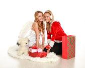 Dvě krásné dívky vánoční dárky a hračky, představují na bílém pozadí — Stock fotografie