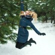 Smiling girl jumping in pinewood, on a winter day — Stock Photo