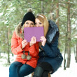 Two smiling girls sitting with a purple box in hands on a winter day — Foto Stock