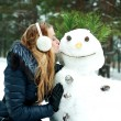 Stock Photo: Pretty girl kissing snowman in pinewood on a winter day