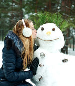 Pretty girl kissing snowman in pinewood on a winter day — Stock Photo