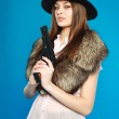 A serious young girl in a black hat with a gun in his hand, in — Stock Photo #19487353