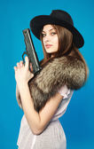 A young brunette in a black hat with a gun in his hand, in the s — Stock Photo