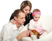 Young parents and baby read the magazine, in the studio — Stok fotoğraf