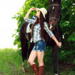 Outdoor portrait of beautiful cowgirl  with horse in green - Stock Photo