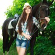 Outdoor portrait of beautiful cowgirl with horse in green — Stock Photo #25117145