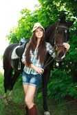 Outdoor portrait of beautiful cowgirl with horse in green — Stock Photo