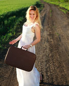 Beautiful blonde girl in long white dress with suitcase — Stock Photo