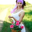 Adorable girl with basket flowers poses in a field — Stock Photo