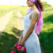 Lonely thoughtfully girl with basket flowers poses in a field — Stock Photo