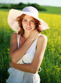 Attractive girl in a summer hat posing on a green glade — Stock Photo