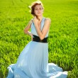 A young woman in a long blue dress enjoying a sunny day — Stock Photo