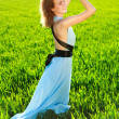 A young woman in a long blue dress enjoying nature — Stock Photo