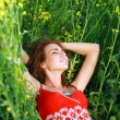 Dreaming girl with closed eyes lying on the field of green grass — Stock Photo