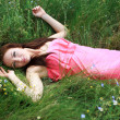 Beautiful young girl dreams, lying on the meadow in spring — Foto Stock