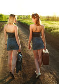 Two girls walking along the road at sunset — Stock Photo