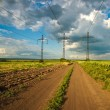 Country landscape with road, clouds and high voltage post and electric wire. — Stock Photo