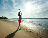 Young slim woman, exercise on the beach at sunrise — Stock Photo