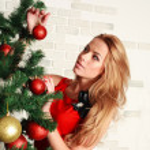 Pretty woman with christmas tree — Stock Photo