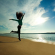 Woman jumping on the beach on sunny sky background — Stock Photo