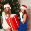 Two girlfriends with a gift near the Christmas tree — Stok fotoğraf