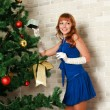 Happy caucasian woman blond with red gift near christmas tree — Stock Photo