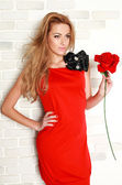 Blond woman with red rose in studio, girl and flower — Stock Photo