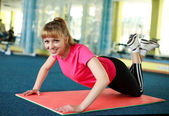 Young woman doing stretching exercise in the gym centre — Stock Photo