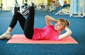 Jonge vrouw doen stretching oefening in de sportschool centrum — Stockfoto