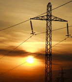 High power electric line towers at dramatic sunset background — Foto Stock