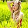 Beautiful summer young woman in green grass, enjoying nature — Stock Photo #45767609