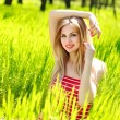 Beautiful summer young woman in green grass, enjoying nature — Stock Photo #45767633