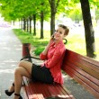 Young woman sitting in a park on a bench talking on the phone — Stock Photo
