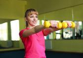 Спортивная девушка, делать упражнения с гантелями в тренажерном зале — Стоковое фото