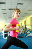 Sporty girl doing exercise with dumbbells in the gym — Foto de Stock