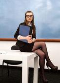 Atractivo joven profesora se sienta en su escritorio en la clase — Foto de Stock