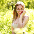 Sensual young woman, smiles sweetly in the flowered garden — Stock Photo #47438353