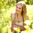 Sensual young woman, smiles sweetly in the flowered garden — Stock Photo #47438533