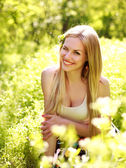 Sensual young woman, smiles sweetly in the flowered garden — Stock Photo