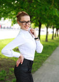 Happy business lady in white shirt and glasses, in a green park — Stock Photo