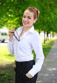 Happy smiling business lady in white shirt, in a green park — Stock Photo