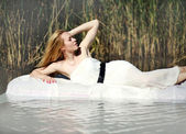 Young woman lies on a white water bed, relaxing outdoors — Photo
