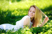 Pensive young woman lying in the green grass, enjoying summer sunny day — Stock Photo