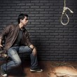 Dramatic lighting photo of young adult considering suicide with a hangman&#039;s - 