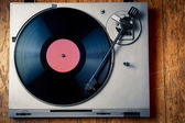 Vintage turntable with disc on wood — Stock Photo