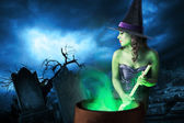Witch with her cauldron on Halloween night — Stock Photo