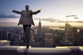 Businessman standing with open arms on top of NY city — Stock Photo